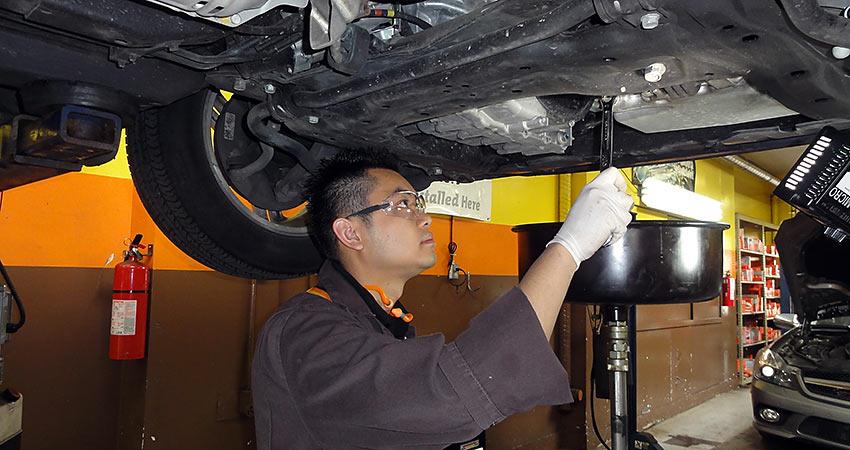 mechanic changing car oil